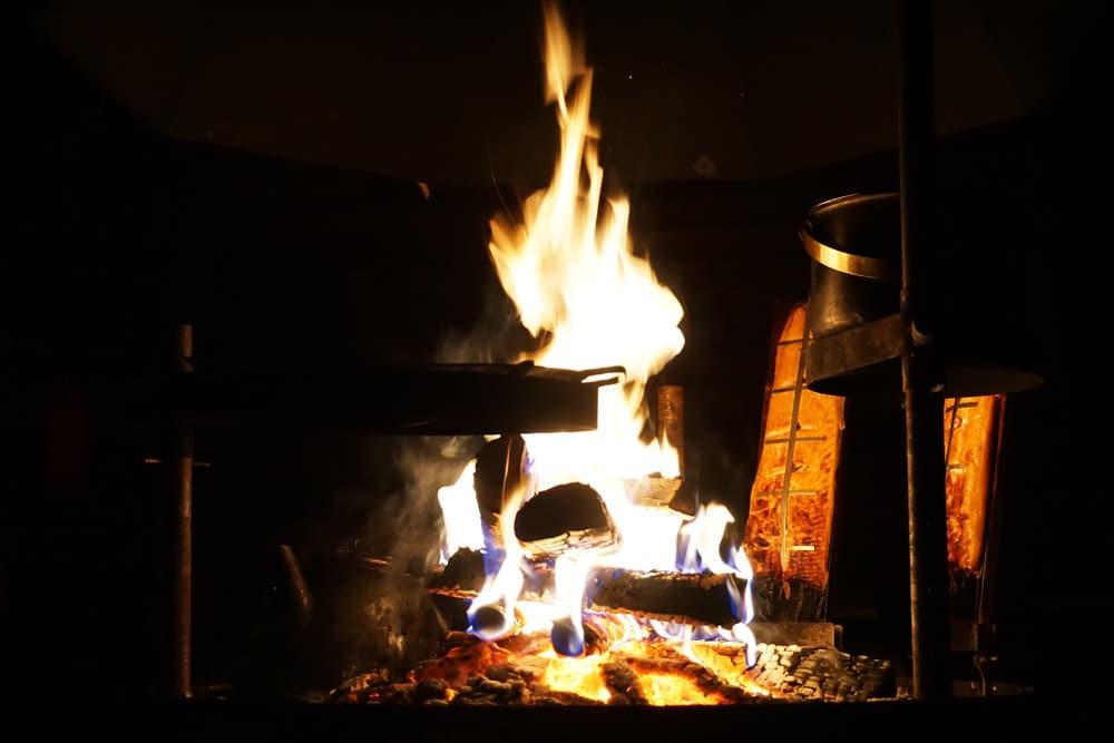 Lachs auf offenem Feuer grillen in der Hütte mit Koliactiv Oy in Koli, Finnland